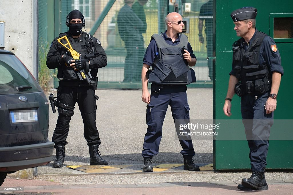 Members of the regional intervention and security teams (ERIS) and French Gendarmerie stand guard at the entrance of the Ensisheim prison, northeastern France, as a psychologist is taken hostage by a prisoner on June 30, 2016. / AFP / SEBASTIEN