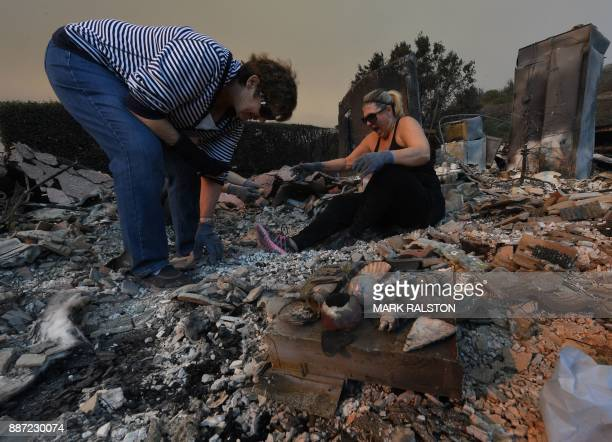 TOPSHOT Members of the Reinhardt family sort through the remains of their family home after the Thomas wildfire swept through Ventura California on...