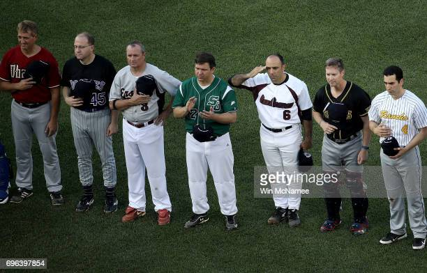 Members of the Republican and Democratic congressional baseball teams stand at attention during the playing of the national anthem before the start...