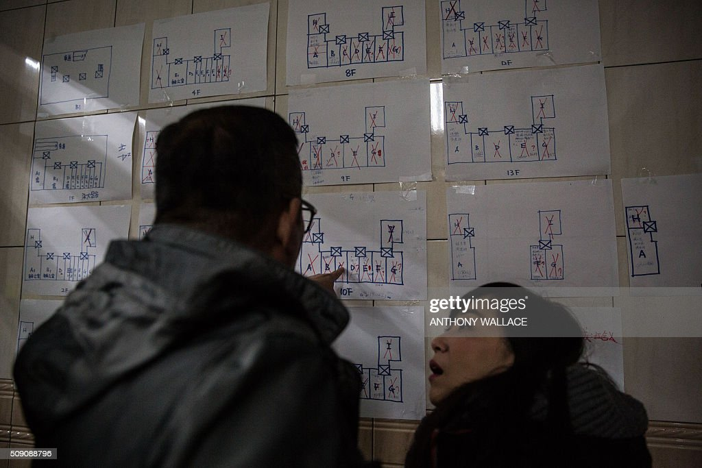 Members of the rescue team look at plans of each floor to see which flats have been checked by rescue workers searching a building which collapsed in the 6.4 magnitude earthquake, in the southern Taiwanese city of Tainan early on February 9, 2016. Rescuers are set to start using diggers and extractors to remove giant concrete slabs once they have ensured all residents from the upper parts of the rubble have been freed. AFP PHOTO / ANTHONY WALLACE / AFP / ANTHONY WALLACE