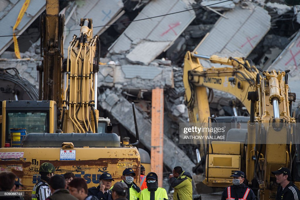 Members of the rescue team stand in front of a cordon near a building (background) which collapsed in the 6.4 magnitude earthquake, in the southern Taiwanese city of Tainan early on February 9, 2016. Rescuers are set to start using diggers and extractors to remove giant concrete slabs once they have ensured all residents from the upper parts of the rubble have been freed. AFP PHOTO / ANTHONY WALLACE / AFP / ANTHONY WALLACE
