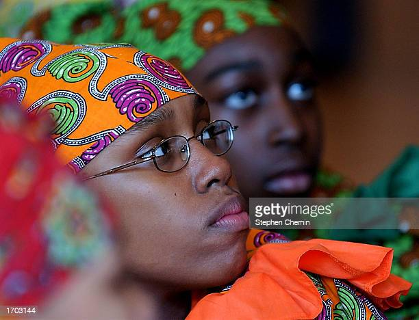 Members of the Restoration Dance Company watch the festivities during a Kwanzaa festival at the Museum of Natural History December 28 2002 in New...