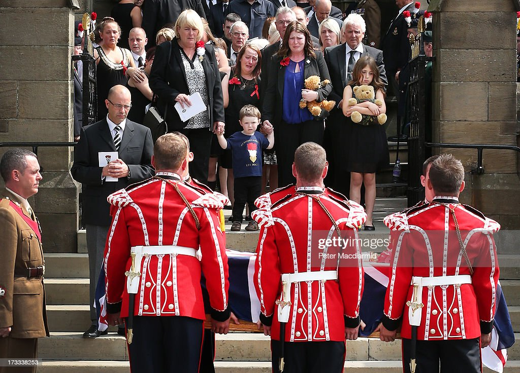 Members of the Rigby family including his son Jack and his wife Rebecca watch as the coffin of Fusilier Lee Rigby leaves Bury Parish Church after his...