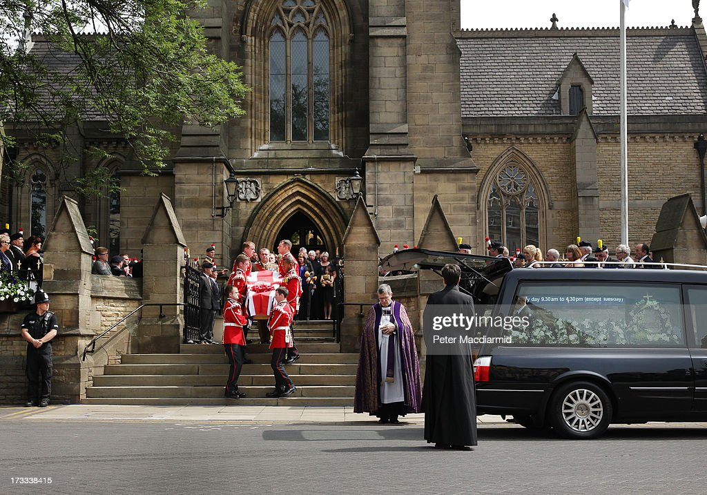 Members of the Rigby family watch as the coffin of Fusilier Lee Rigby leaves Bury Parish Church after his military funeral on July 12 2013 in Bury...