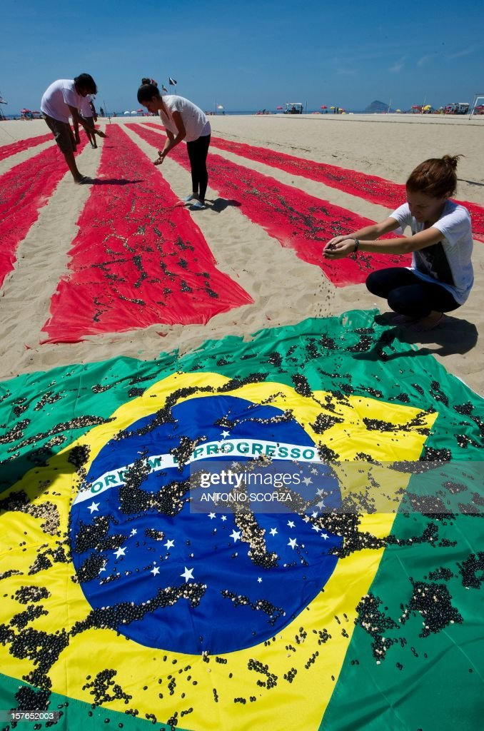 Members of the Rio of Peace NGO throw black and white beans over a Brazilian flag during a protest against the half a million homicides occured in the last 10 years in the country, on December 5, 2012 at Copacabana Beach in Rio de Janeiro, Brazil. AFP PHOTO/ANTONIO SCORZA