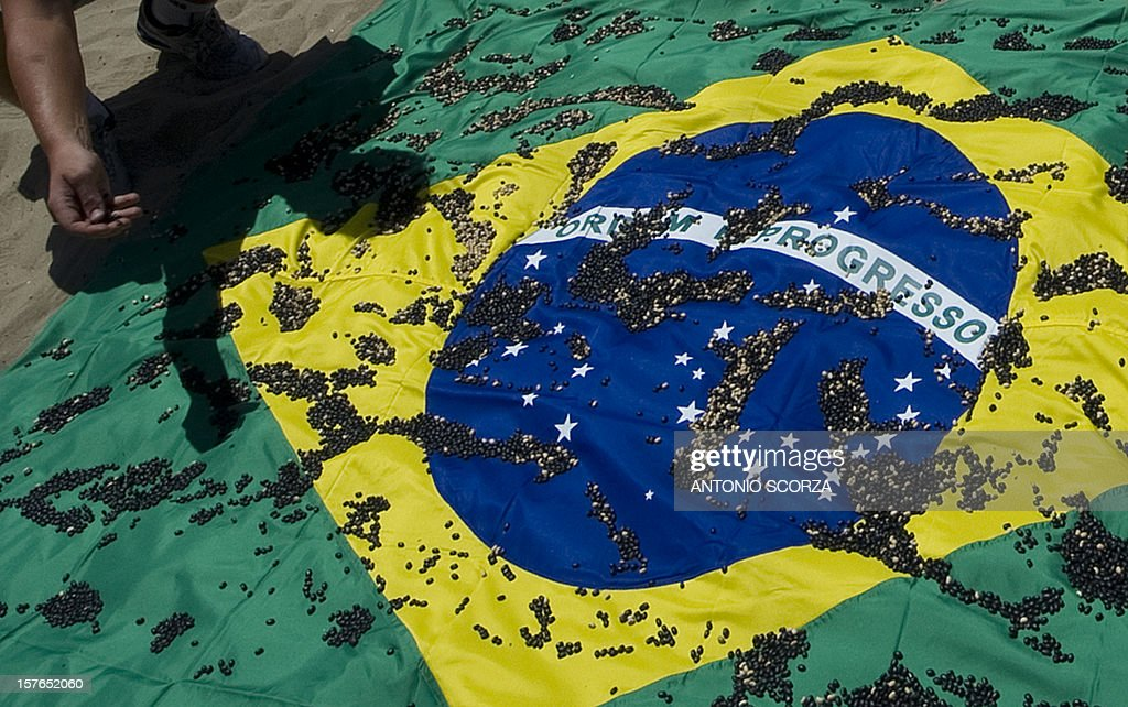 Members of the Rio of Peace NGO throw black and white beans over a Brazilian flag during a protest against the half a million homicides occured in the last 10 years in the country, on December 5, 2012 at Copacabana Beach in Rio de Janeiro, Brazil.