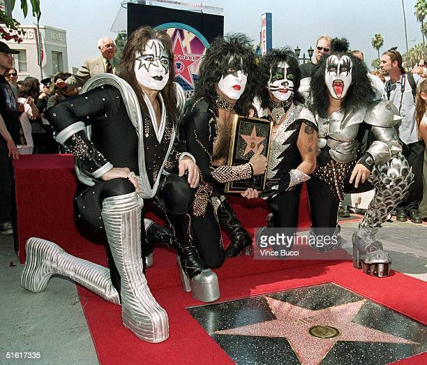 Members of the rock band Kiss Ace Frehley Paul Stanley Peter Criss and Gene Simmons pose by the star they received during a Hollywood Walk of Fame...