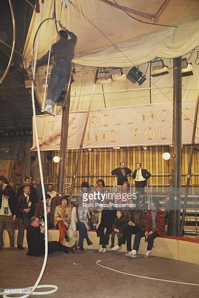Members of the Rolling Stones and friends watch a trapeze artist perform during rehearsals for the Rolling Stones Rock and Roll Circus at Internel...