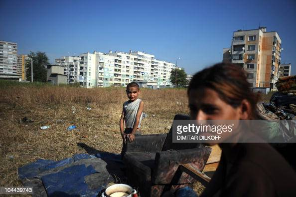 Members of the Roma community look on in a makeshift camp as the huge holedout shell of an apartment building and the pungent stench of tons of...