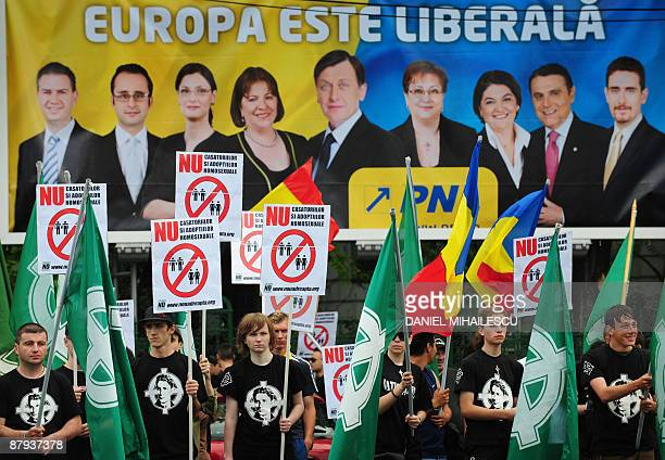 Members of the Romanian far right organisation 'Noua Dreapta' are pictured holding signs reading 'NO to homosexual marriages and adoptions'...