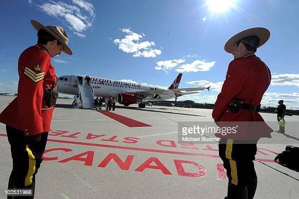 Members of the Royal Canadian Mounted Police stand gaurd in front of 'Air Drake' to celebrate Virgin America's first international flight to Toronto...
