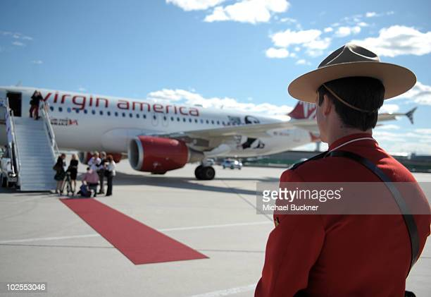 A members of the Royal Canadian Mounted Police stands gaurd in front of 'Air Drake' to celebrate Virgin America's first international flight to...