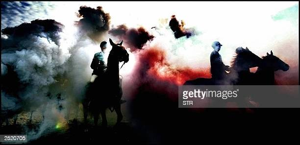 Members of the Royal Guard ride on their horses through clouds of colored smoke and gunfire on the beach of Scheveningen near The Hague during...
