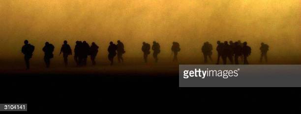Members of the Royal Irish Rangers march in the Kuwaiti desert 19 March 2003 as they head towards Iraq AFP PHOTO POOL