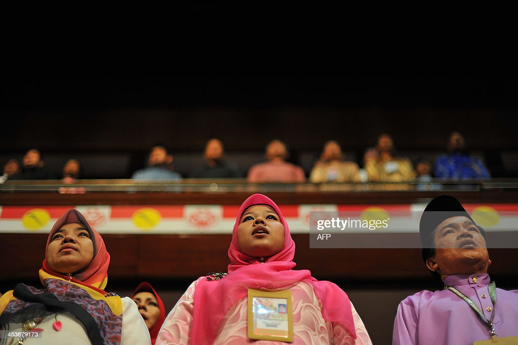 Members of the ruling party United Malays National Organisation (UMNO) sing the party's anthem during the opening ceremony of the annual general assembly at the Putra World Trade Center (PWTC) in Kuala Lumpur on December 5, 2013. The ruling party UMNO's six day general assembly 2013 began with the official opening by the party President Najib Razak.