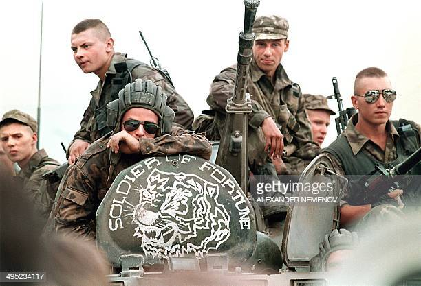 Members of the Russian Army sit atop an armored personal vehicle with a logo of 'Soldier of Fortune' 18 July 1995 in Grozny capital of the breakaway...