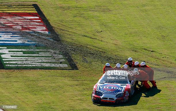 Members of the safety crew push DJ Kennington driver of the NPPL/Vector Dodge out of the muddy infield during the NASCAR BUSCH Series Sam's Town 250...