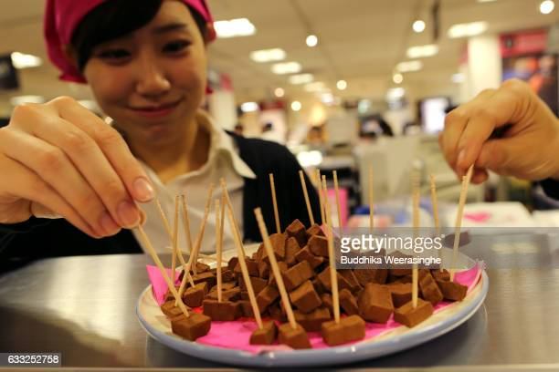 Members of the sales staff arrange samples of Valentine's Day chocolate pieces for customers at a Takashimaya Department Store on February 1 2017 in...