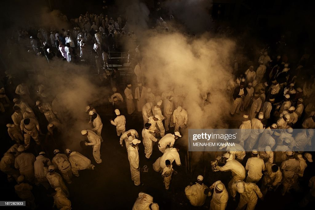 Members of the Samaritan community seal the oven after placing as slaughtered sheep during the traditional Passover sacrifice ceremony at Mount Gerizim near the northern West Bank city of Nablus on April 23 2013. The Samaritan community, comprising about 720 people, practices a religion that is based on the Torah -- the first five books of the Bible and one holy place. AFP PHOTO/Menahem Kahana