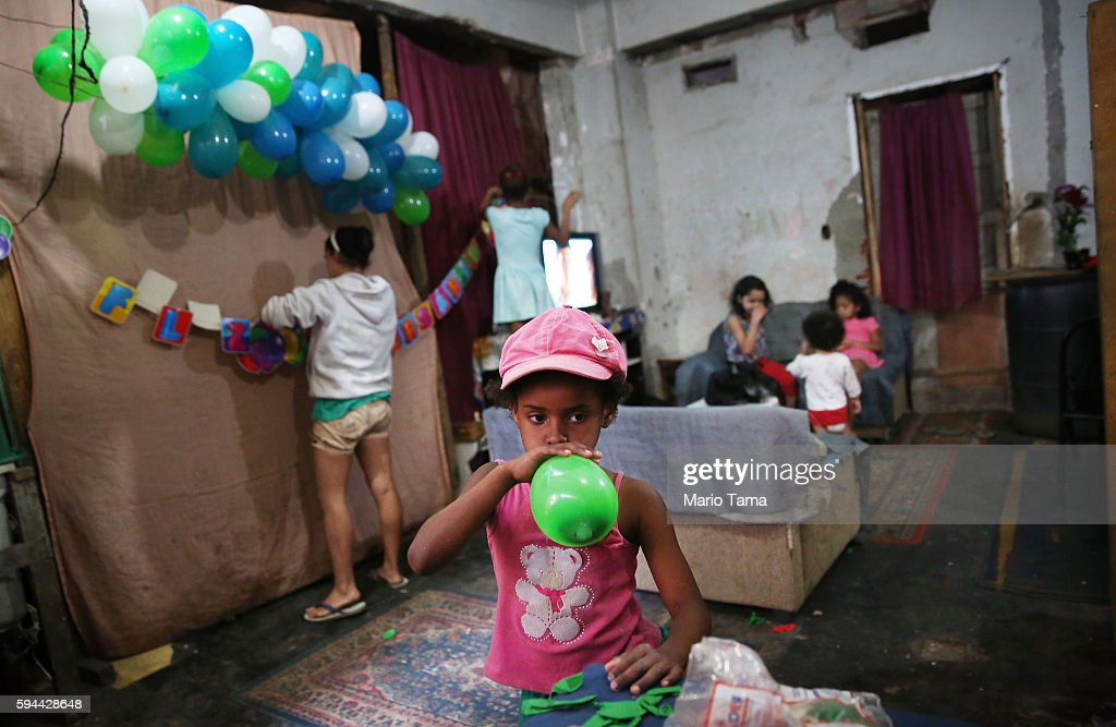 Members of the Sampaio family and friends make preparations for a birthday party in an occupied building in the Mangueira 'favela' community on August 23, 2016 in Rio de Janeiro, Brazil. The closing ceremonies of the Rio 2016 Olympic Games were held in nearby Maracana stadium.
