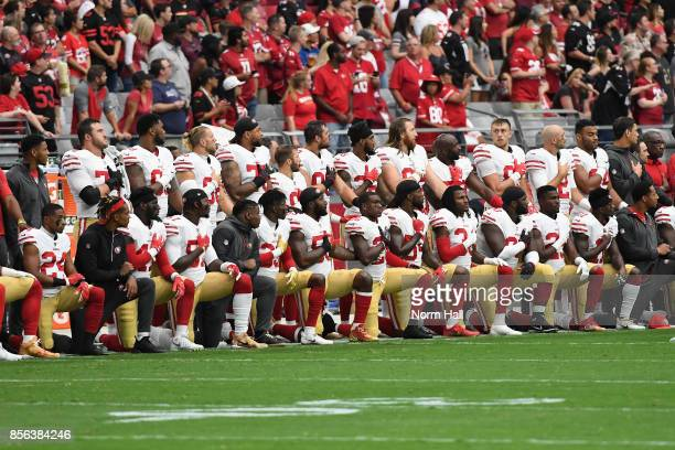 Members of the San Francisco 49ers kneel for the National Anthem before the start of the NFL game against the Arizona Cardinals at the University of...
