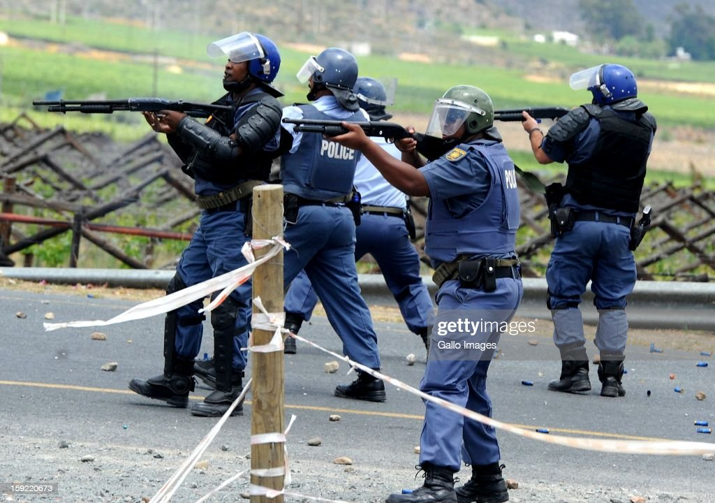 Members of the SAPD take action at the N1 De Doorns protest on January 9, 2013, in Cape Town, South Africa. Protesting farm workers shut down the N1 by lighting tires on fire and placing large rocks on the road.