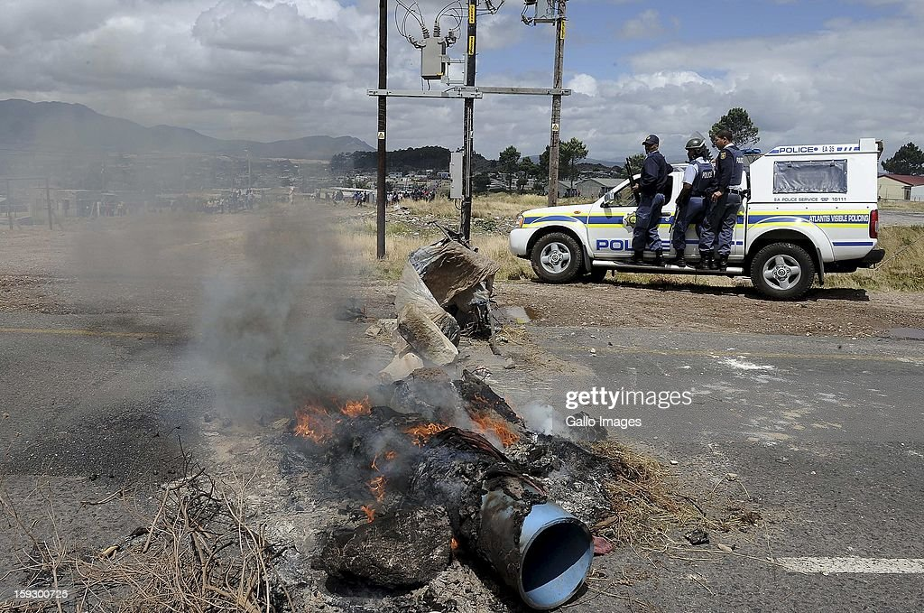 Members of the SAPS on the N2 highway on January 10, 2013 in Grabouw, South Aifrca. Striking farm workers have blocked the highway as they continue striking.