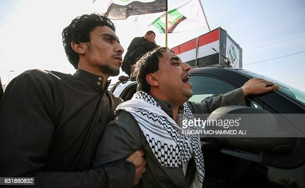 TOPSHOT Members of the Saraya alSalam a group formed by Iraqi Shiite Muslim cleric Moqtada alSadr grieve in a procession alongside a coffin during...