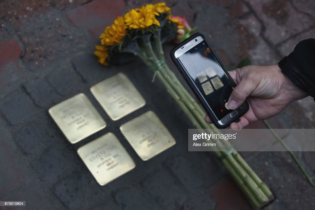 Members of the scattered Cohn family lay down flowers after German artist Gunter Demnig layed four 'stumbling stones' to commemorate Jewish schoolgirl and Holocaust victim Karolina Cohn and her family outside the building where they once lived on November 13, 2017 in Frankfurt, Germany. Karolina's fate came to light after Israeli archeologists digging at the former World War II Sobibor concentration camp found an amulet inscribed with Karolina's birthdate and birthplace, which helped them to confirm that she and her family were killed there. The Nazis deported Karolina, then 12, and her family to Minsk in 1941, though the rest of their journey had been unknown until now. Approximately 30 members of the Cohn family came from the United States, Israel, Japan and Canada to attend today's ceremonies. 'Stumbling stones,' in German called 'Stolpersteine,' are commemorative cobblestones affixed with a brass plate with the names of victims laid in the sidewalks outside the former residences of Jews in Germany killed in the Holocaust.