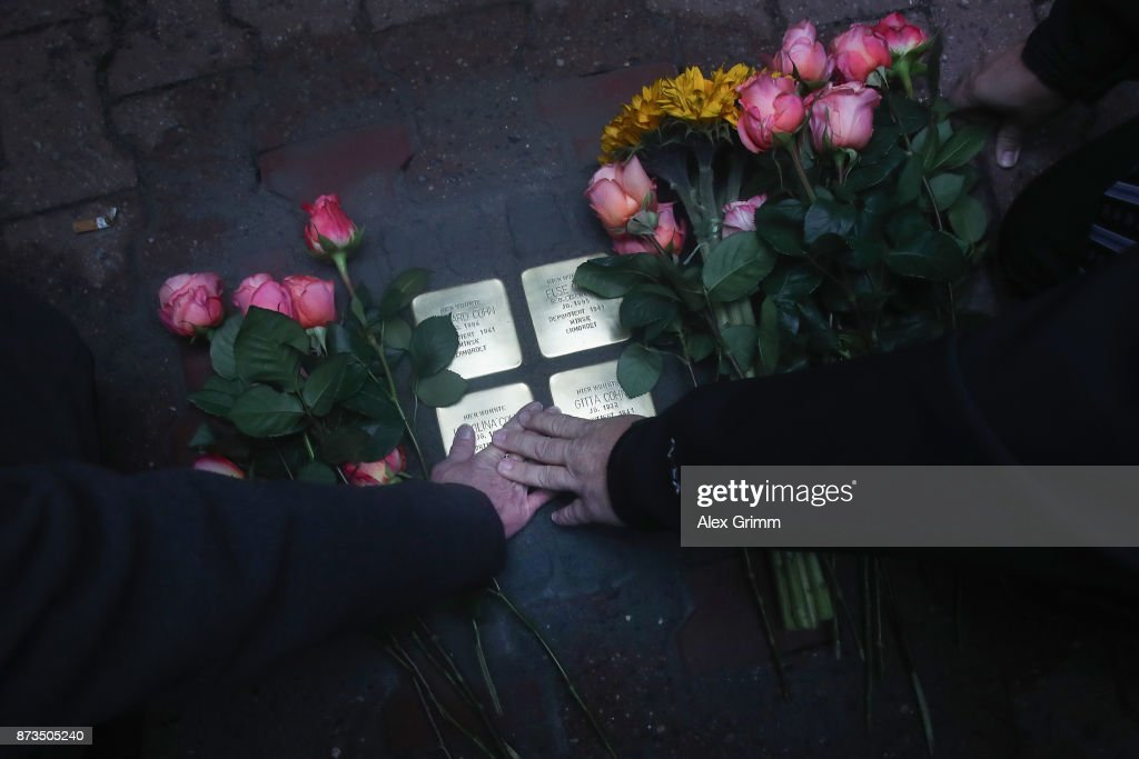 Members of the scattered Cohn family mourn after German artist Gunter Demnig layed four 'stumbling stones' to commemorate Jewish schoolgirl and Holocaust victim Karolina Cohn and her family outside the building where they once lived on November 13, 2017 in Frankfurt, Germany. Karolina's fate came to light after Israeli archeologists digging at the former World War II Sobibor concentration camp found an amulet inscribed with Karolina's birthdate and birthplace, which helped them to confirm that she and her family were killed there. The Nazis deported Karolina, then 12, and her family to Minsk in 1941, though the rest of their journey had been unknown until now. Approximately 30 members of the Cohn family came from the United States, Israel, Japan and Canada to attend today's ceremonies. 'Stumbling stones,' in German called 'Stolpersteine,' are commemorative cobblestones affixed with a brass plate with the names of victims laid in the sidewalks outside the former residences of Jews in Germany killed in the Holocaust.