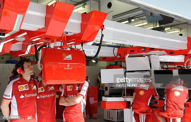 Members of the Scuderia Ferrari team watch the third practice session on screens in the pits ahead of the Formula One Bahrain Grand Prix at the...