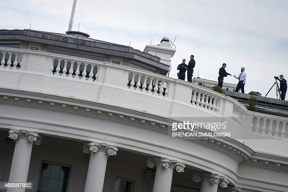 Members of the Secret Service are seen on the roof of the White House March 17 2015 in Washington DC AFP PHOTO/BRENDAN SMIALOWSKI