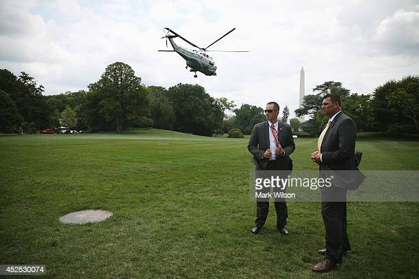 Members of the Secret Service stand guard as Marine One carrying US President Barack Obama takes off from south lawn of the White House July 22 2014...