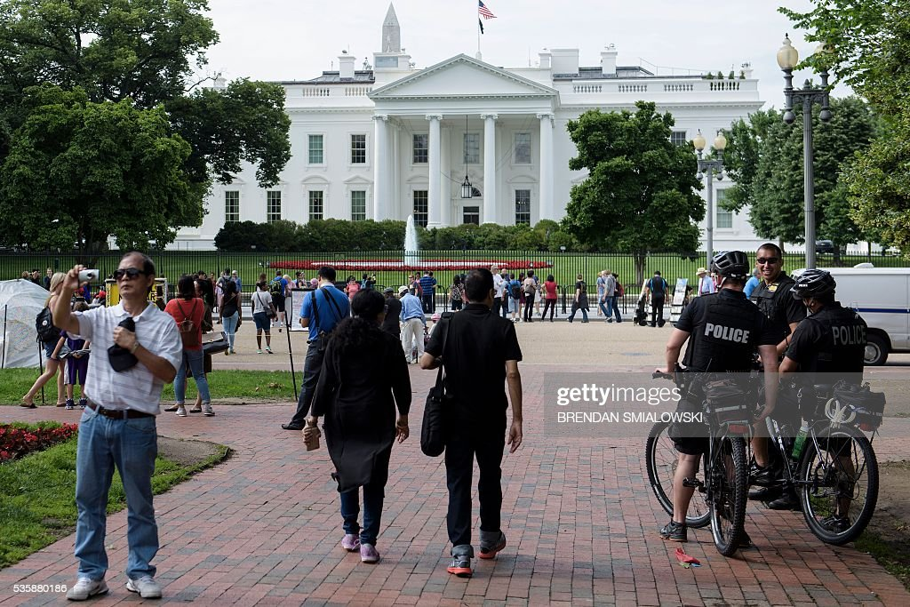 Members of the Secret Service talk to each other as people visit the grounds around the White House May 30, 2016 in Washington, DC. / AFP / Brendan Smialowski