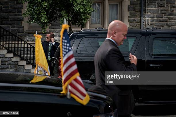 Members of the Secret Service watch over armored vehicles while Pope Francis visits St Patrick's Catholic Church September 24 2015 in Washington DC...