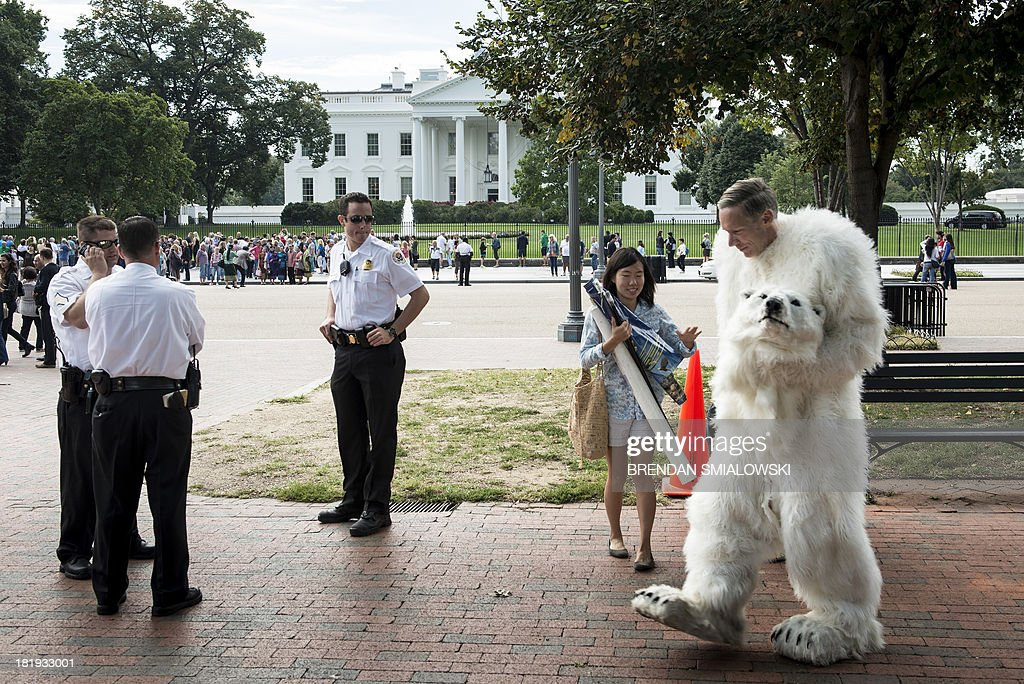 Members of the Secret Service's Uniformed Division look at an activist partially dressed as a polar bear before a protest in Lafayette Park September 26, 2013 in Washington, DC. Environmental activists gathered to protest the practice of arctic drilling and pressure the Obama administration to do the same. AFP PHOTO/Brendan SMIALOWSKI