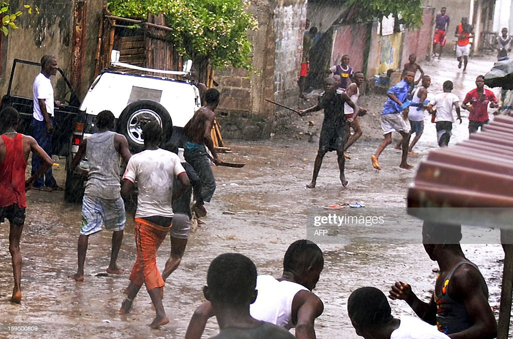 Members of the Secteur du Rail Aunts 'Kuluna' (street children gang) fight with members of the Likonzi Kuluna (in the background) on December 14, 2012 in a street of Lingwala, north of Kinshasa. The modus operandi of kuluneurs is the following: either in broad daylight or at night, a pack of martial arts practitioners (called pombas) armed with clubs, machetes and other blunt objects raid and occupy a city square wherein they seize from passers-by and street vendors any valuable they can lay their hands on. Victims who resist are hacked with machetes, clubbed or stabbed. Some victims have died from injuries sustained in those kuluna raids and many a warlord kuluneur have has been gunned down by the Police dIntervention Rapide (PIR).