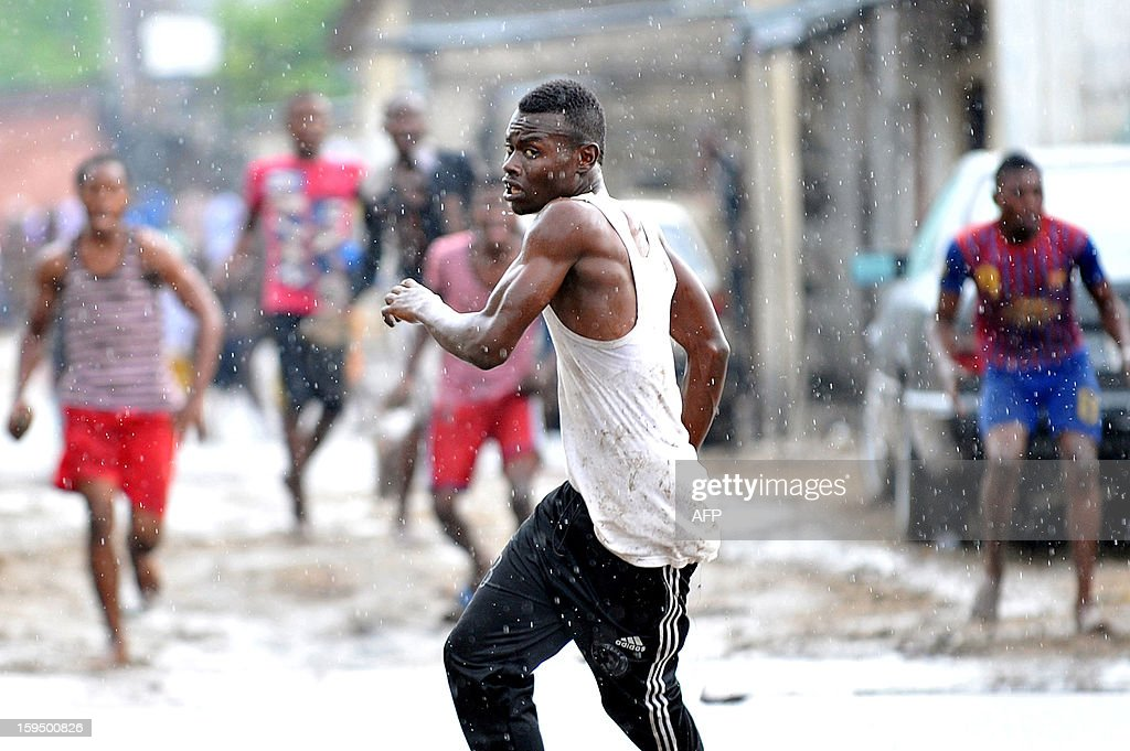 """Members of the Secteur du Rail Aunts 'Kuluna' (street children gang) fight with members of the Likonzi Kuluna (unseen) on November 16, 2012 in a street of Lingwala, north of Kinshasa. The modus operandi of """"kuluneurs"""" is the following: either in broad daylight or at night, a pack of martial arts practitioners (called """"pombas"""") armed with clubs, machetes and other blunt objects raid and occupy a city square wherein they seize from passers-by and street vendors any valuable they can lay their hands on. Victims who resist are hacked with machetes, clubbed or stabbed. Some victims have died from injuries sustained in those kuluna raids and many a warlord kuluneur have has been gunned down by the Police d'Intervention Rapide (PIR)."""
