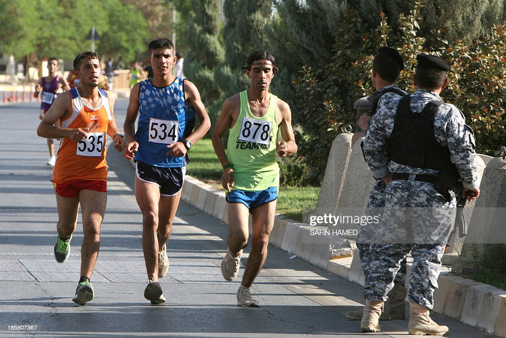 Members of the security forces keep watch as runners compete in the '3rd International Erbil Marathon' in the northern city of Arbil, capital of Iraq's Kurdistan, on October 25, 2013. The marathon was organised under the motto of 'Let us run for peace and development'. AFP PHOTO/SAFIN HAMED