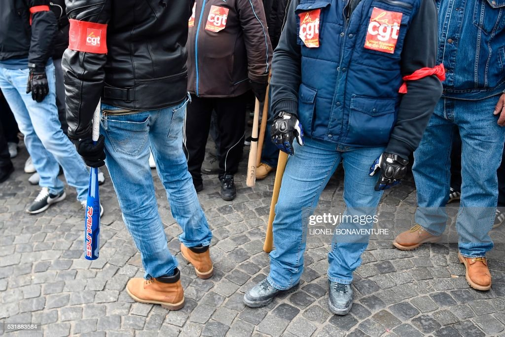 TOPSHOT Members of the security service of French CGT workers' unions hold wooden bars and baseball bats at a demonstration after the French...