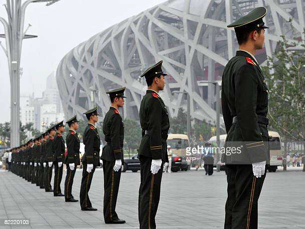 Members of the security stand in front of the National Stadium also known as the 'Bird's Nest' for the 2008 Beijing Olympic Games opening ceremony in...