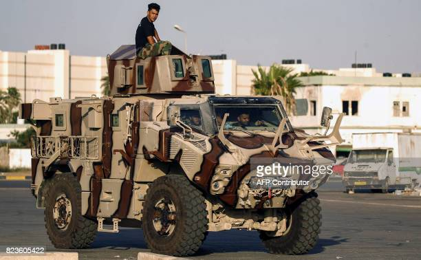 Members of the selfstyled Libyan National Army loyal to the country's east strongman Khalifa Haftar ride in and atop an armoured vehicle in the...