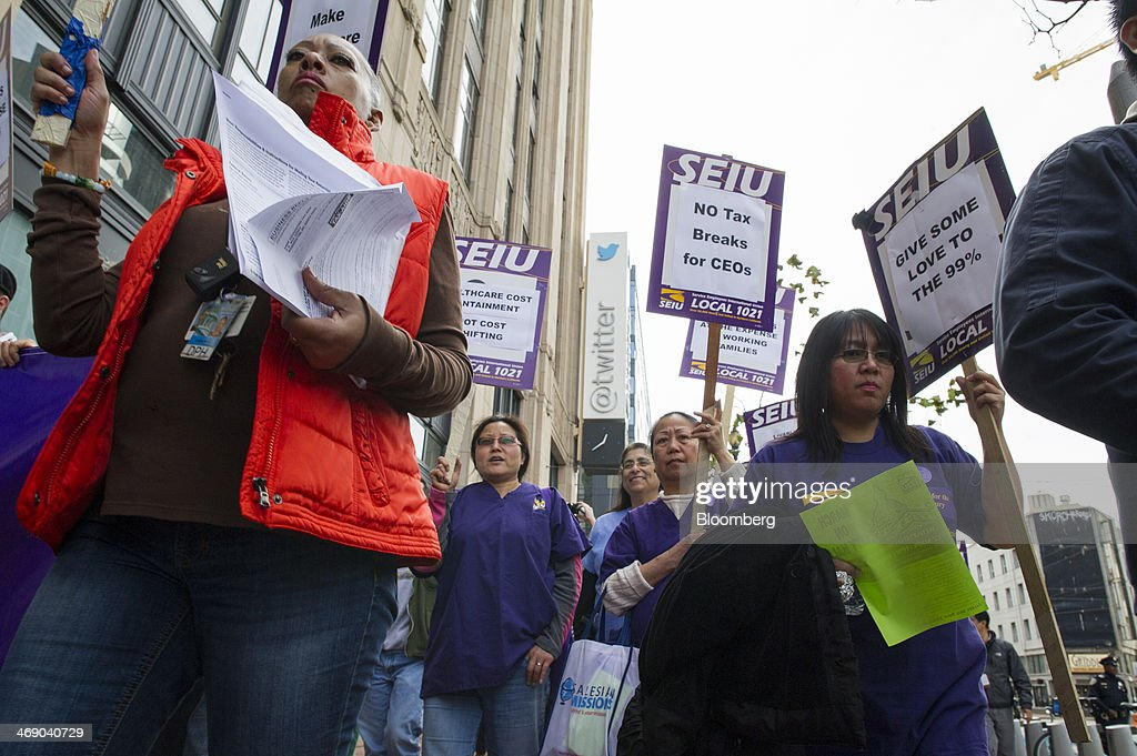 Members of the Service Employees International Union (SEIU) Local 1021 carry signs that read 'No Tax breaks for CEOs' and 'Give Some Love to The 99%' while protesting in front of Twitter Inc. headquarters in San Francisco, California, U.S., on Wednesday, Feb. 12, 2014. City workers represented by SEIU 1021 are participating in an affordable healthcare rally. Photographer: David Paul Morris/Bloomberg via Getty Images