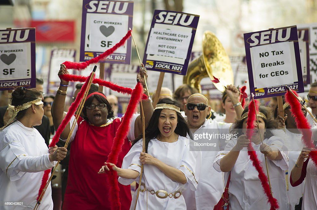 Members of the Service Employees International Union (SEIU) Local 1021 carry signs that read 'No Tax breaks for CEOs' and 'City Workers Love SF' while protesting in front of Twitter Inc. headquarters in San Francisco, California, U.S., on Wednesday, Feb. 12, 2014. City workers represented by SEIU 1021 are participating in an affordable healthcare rally. Photographer: David Paul Morris/Bloomberg via Getty Images