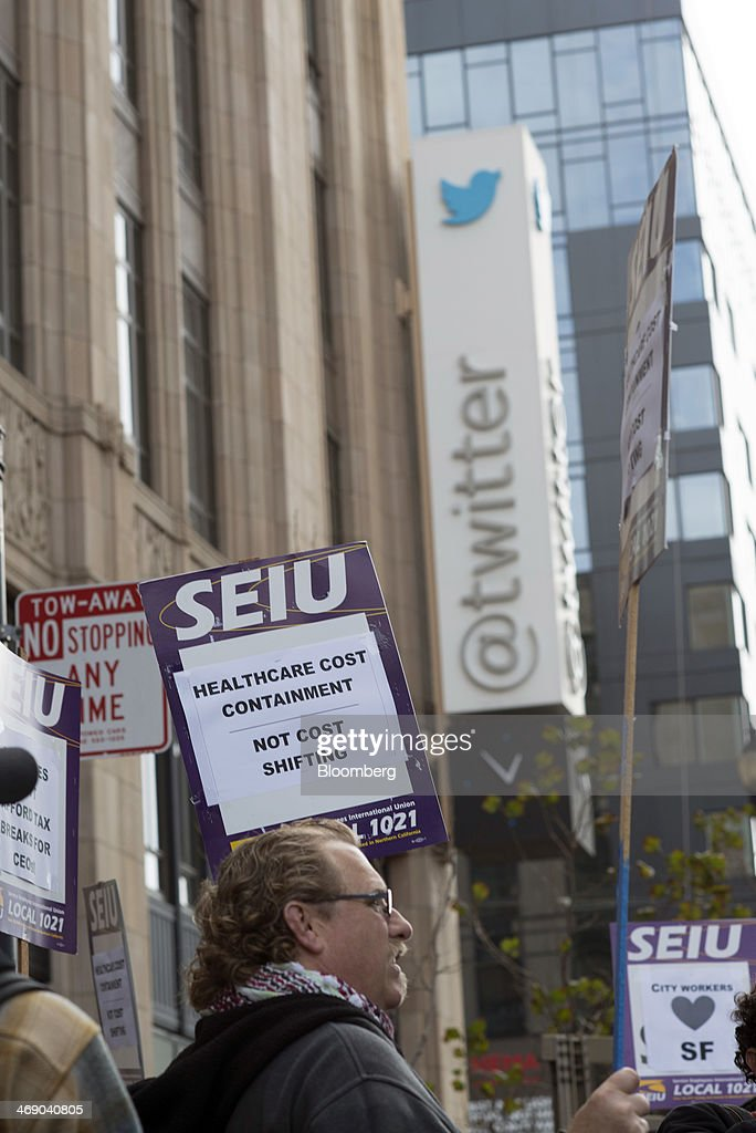 Members of the Service Employees International Union (SEIU) Local 1021 hold signs that read 'City Workers Love SF' and 'Healthcare Cost Containment Not Cost Shifting' while protesting in front of Twitter Inc. headquarters in San Francisco, California, U.S., on Wednesday, Feb. 12, 2014. City workers represented by SEIU 1021 are participating in an affordable healthcare rally. Photographer: David Paul Morris/Bloomberg via Getty Images