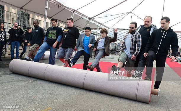 Members of the setup crew are joined by actors Rico Rodriguez and Nolan Gould while rolling out the red carpet in Los Angeles on January 26 2013...