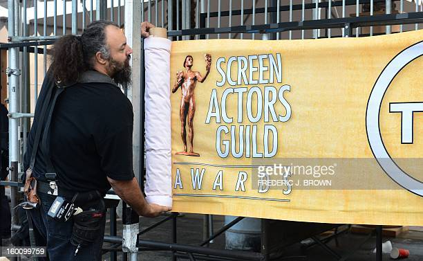 Members of the setup crew hang banners in Los Angeles on January 26 2013 during behind the scenes preparations ahead of the 19th Annual Screen Actors...