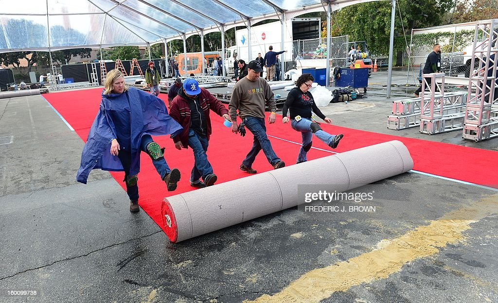 Members of the setup crew roll out the red carpet in Los Angeles on January 26, 2013 during preparations ahead of the 19th Annual Screen Actors Guild (SAG) Awards on January 27. AFP PHOTO/Frederic J. BROWN