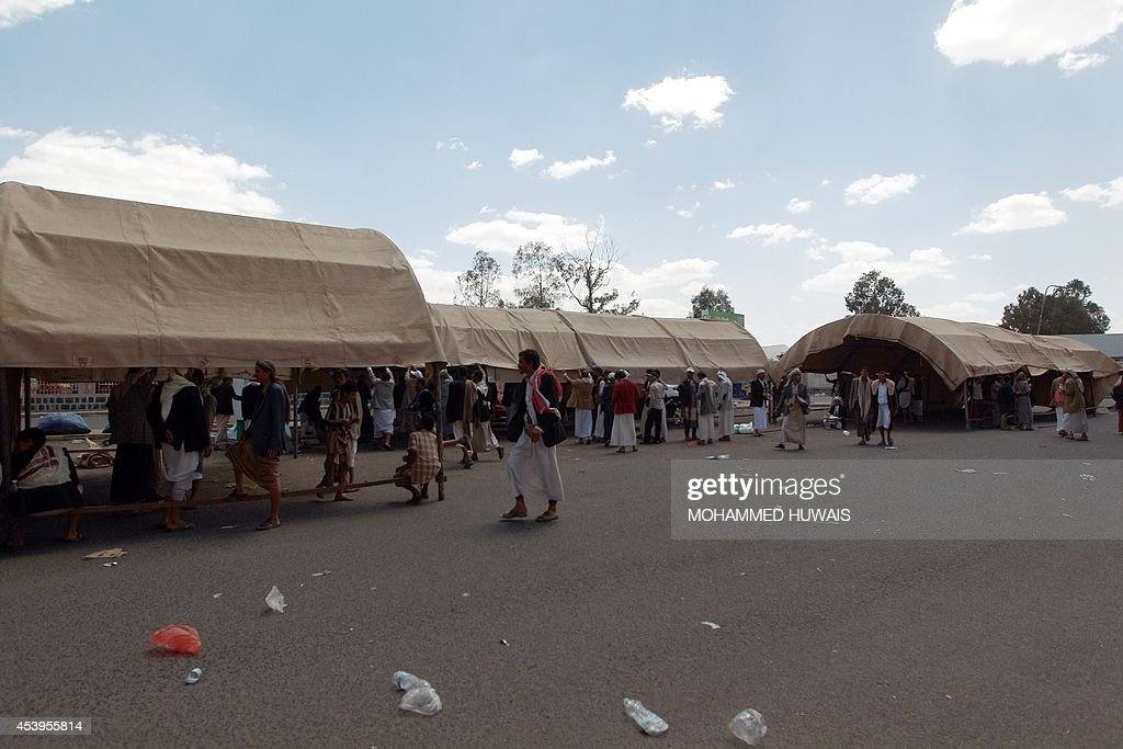 Members of the Shiite Huthi movement walk past tents erected at a sit-in camp on a road leading to Sanaa International Airport as they demand the resignation of the Yemeni government on August 22, 2014, in the Yemeni capital, Sanaa. The Zaidi Shiites, a minority in mainly Sunni Yemen, form the majority in the northern highlands, including the Sanaa region and strongly oppose the government's plans for a six-region federation, demanding a single region for the northern highlands and a greater share of power in the federal government.