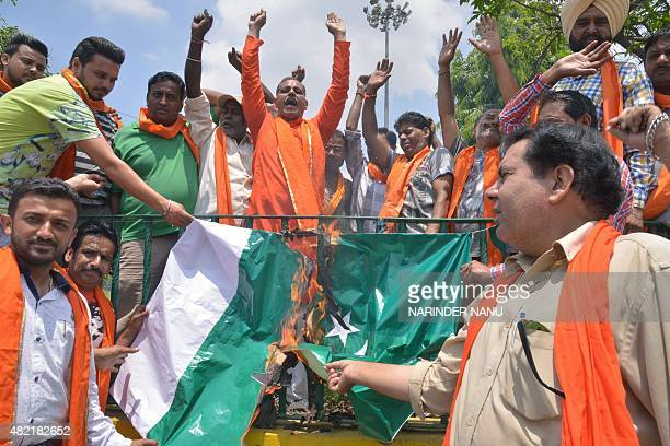 Members of the Shiv Sena nationalist Hindu group shout slogans as they burn a Pakistani flag during a protest in Amritsar on July 28 2015 following a...